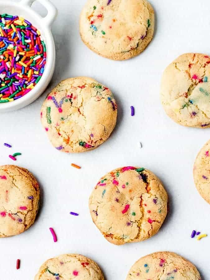 Fluffy Sprinkle Cookies shot from overhead with sprinkles in bowl top left