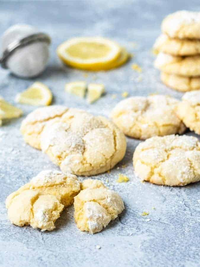 Lemon Crinkle Cookies with one cut in half in front showing texture | kickassbaker.com