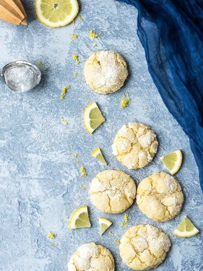 Lemon Crinkle Cookies shot from above with lemon pieces and lemon zest and blue gauze draped on the side | kickassbaker.com