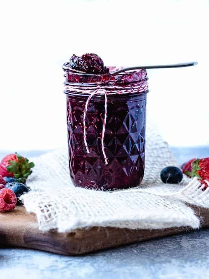 Small Batch Mixed Berry Jam straight on in mason jar with berries on the side and small spoon on top of jar | kickassbaker.com