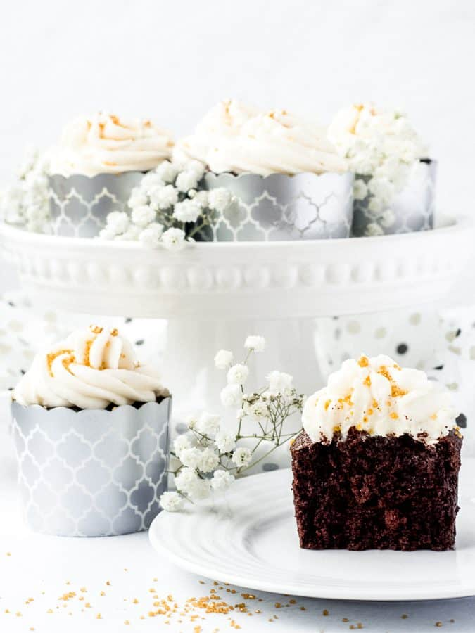 Chocolate Sour Cream Fudge Cupcakes, single cupcake on plate cut in half with cupcakes on cake stand behind and flowers | kickassbaker.com