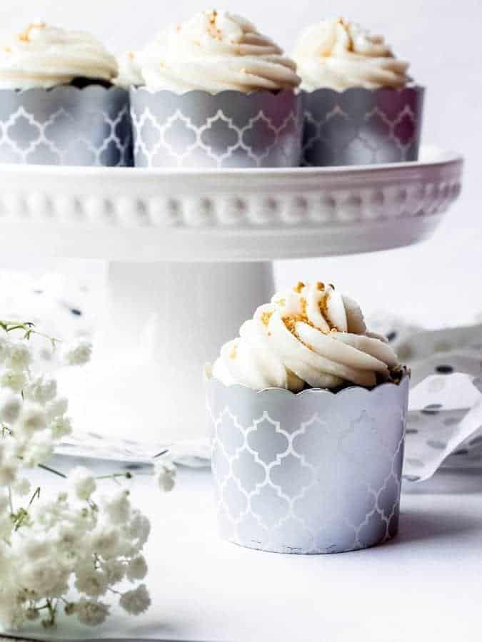 Chocolate Sour Cream Fudge Cupcakes straight on single cupcake with flowers on left   kickassbaker.com