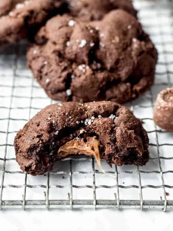 Salted Caramel Stuffed Dark Chocolate Cookies close up of bitten cookie with caramel spilling out of center | kickassbaker.com