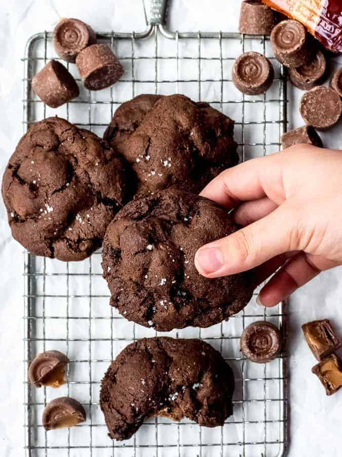 Salted Caramel Stuffed Dark Chocolate Cookies overhead shot of cookies on cooling rack, picking one up | kickassbaker.com