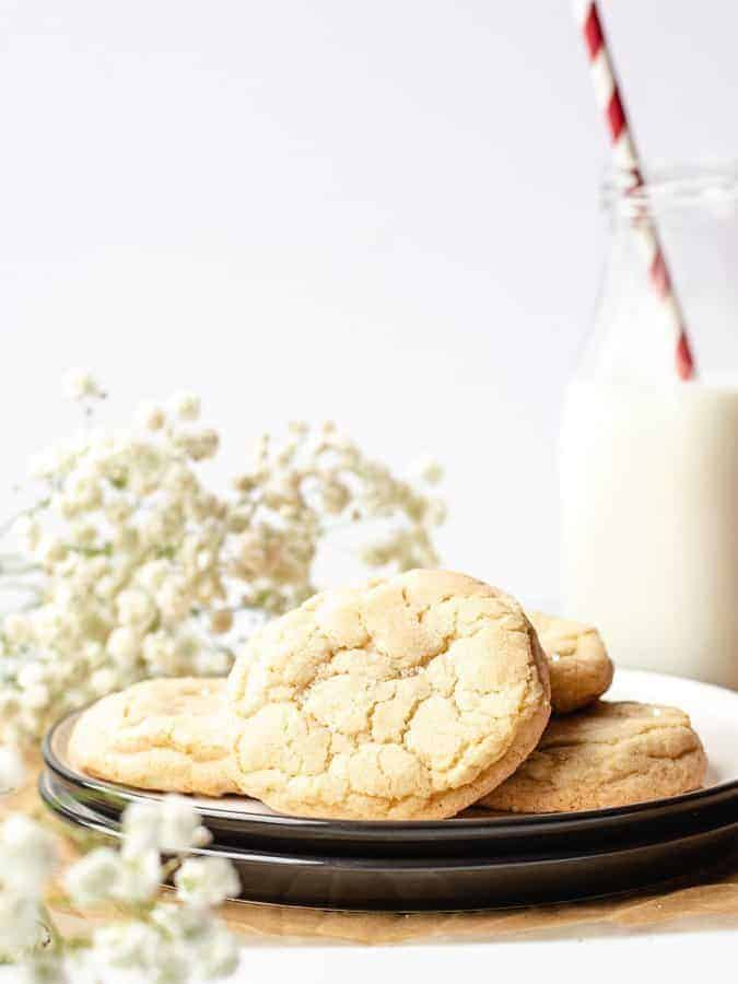 Straight on shot of Soft and Chewy Sugar Cookies on two stacked plates with flowers in background and a glass of milk with a red and white straw
