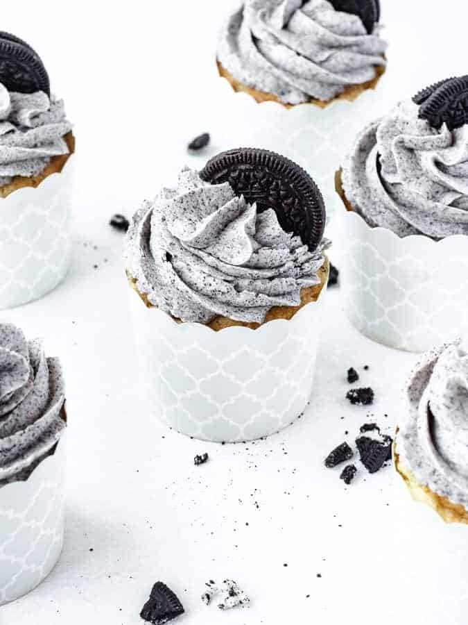 45 degree angle shot of Oreo cupcakes on a white surface with Oreo cookies scattered around