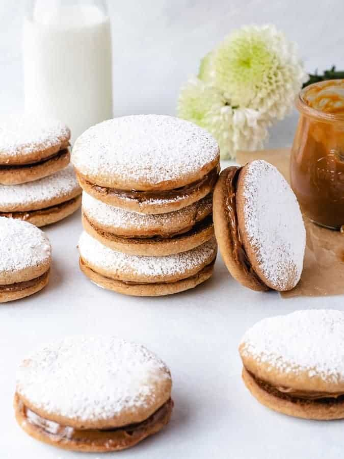 Alfajore sandwich cookies with dulce de leche filling stacked with jar to the right and milk and flowers behind