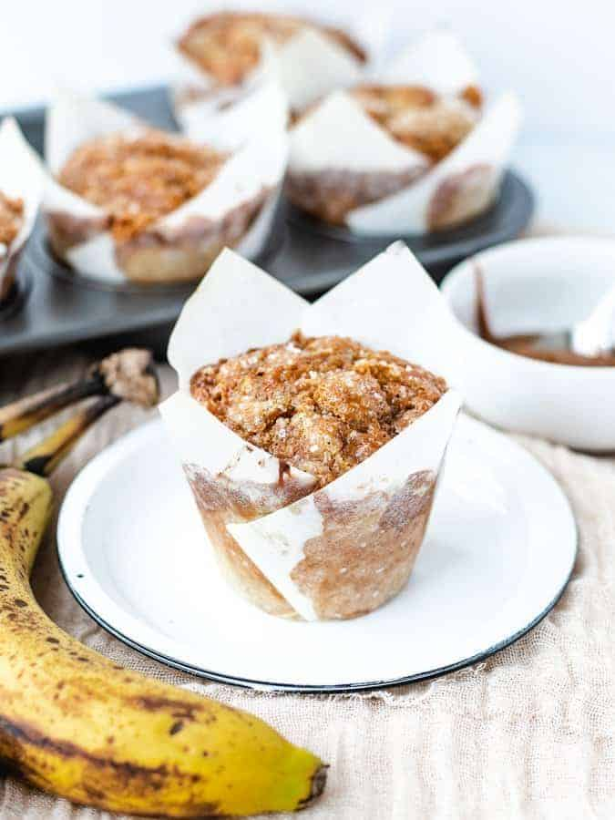 Banana muffin on a plate with pan of muffins behind and banana and dulce de leche off to the sides