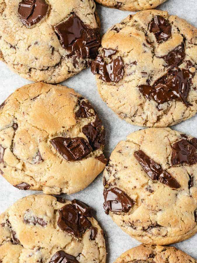 Overhead shot of large chocolate chip cookies with pools of melted dark chocolate