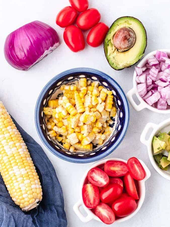 Overhead shot of ingredients for corn salad in separate bowls ready to be added together to make a salad