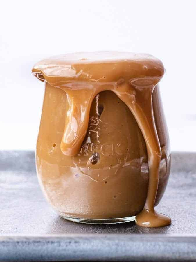 Easy Homemade Dulce de Leche | kickassbaker.com overflowing jar of smooth caramel