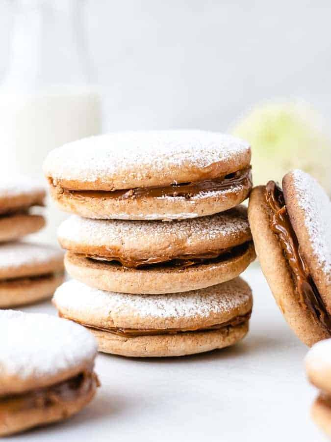 Alfajore sandwich cookies close up of 3 cookies stacked and one leaning against the stack