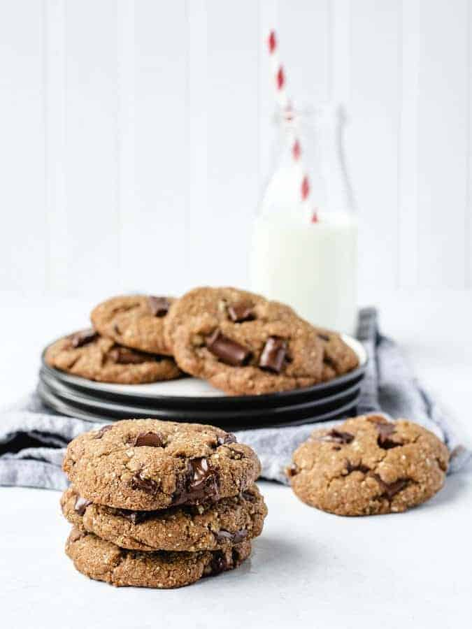 stack of 3 paleo chocolate chip cookies with some on a plate and jug of milk behind