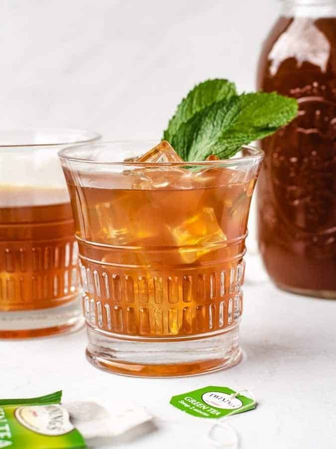 Glass of sweet mint iced tea paleo with fresh mint leaves in it and ice cubes