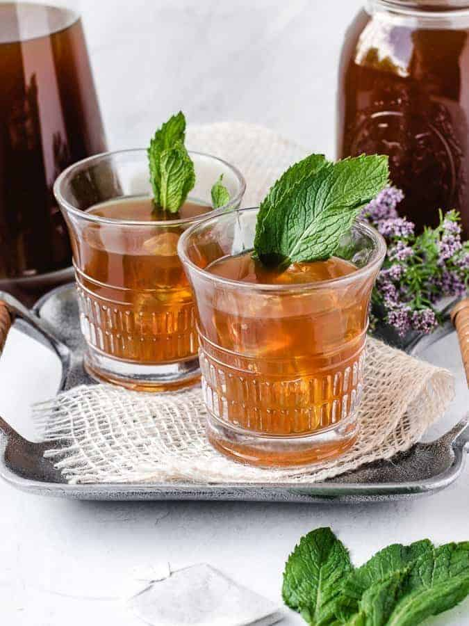two glasses of paleo sweet mint iced tea on a tray with fresh mint leaves and purple flowers behind