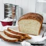 Classic easy homemade amish white bread partially sliced on a cutting board