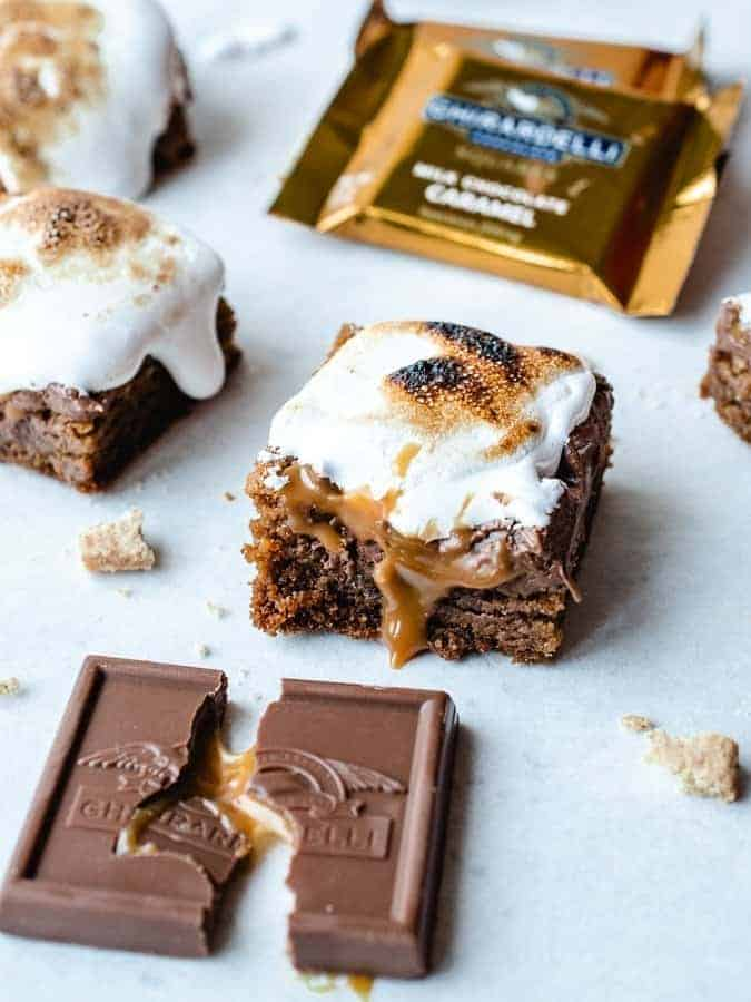 Caramel S'mores bars cut into squares with burnt marshmallow on top and caramel oozing out
