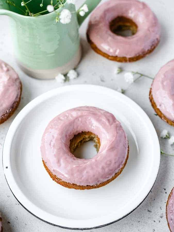 Baked Donuts with pink chocolate glaze on a plate with flowers behind