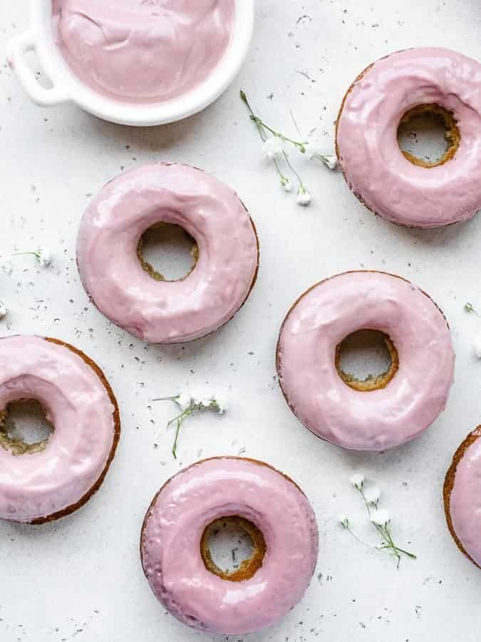Overhead shot of baked donuts with pink ruby chocolate glaze and white flowers spread across