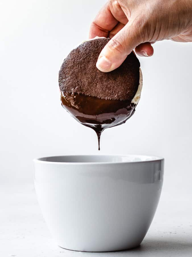 Dipping a chocolate cookie ice cream sandwich in melted chocolate