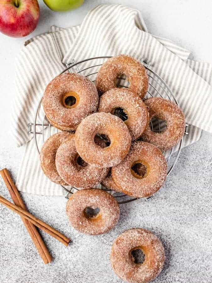 Overhead shot of apple cider donuts on a wire rack with cinnamon and apples