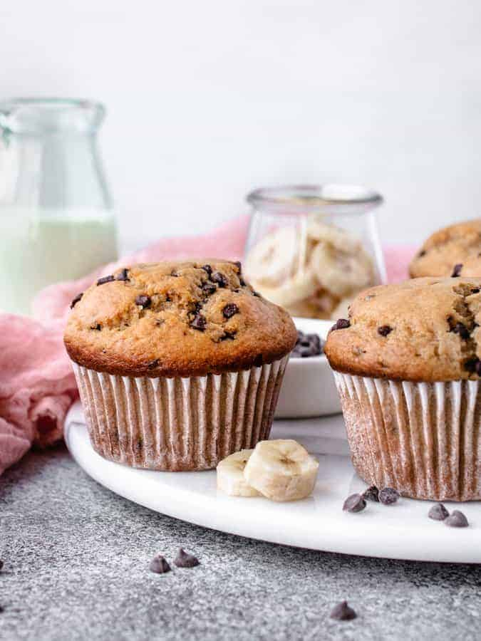Banana Chocolate Chip Muffins on a marble board with sliced bananas and mini chocolate chips sprinkled around
