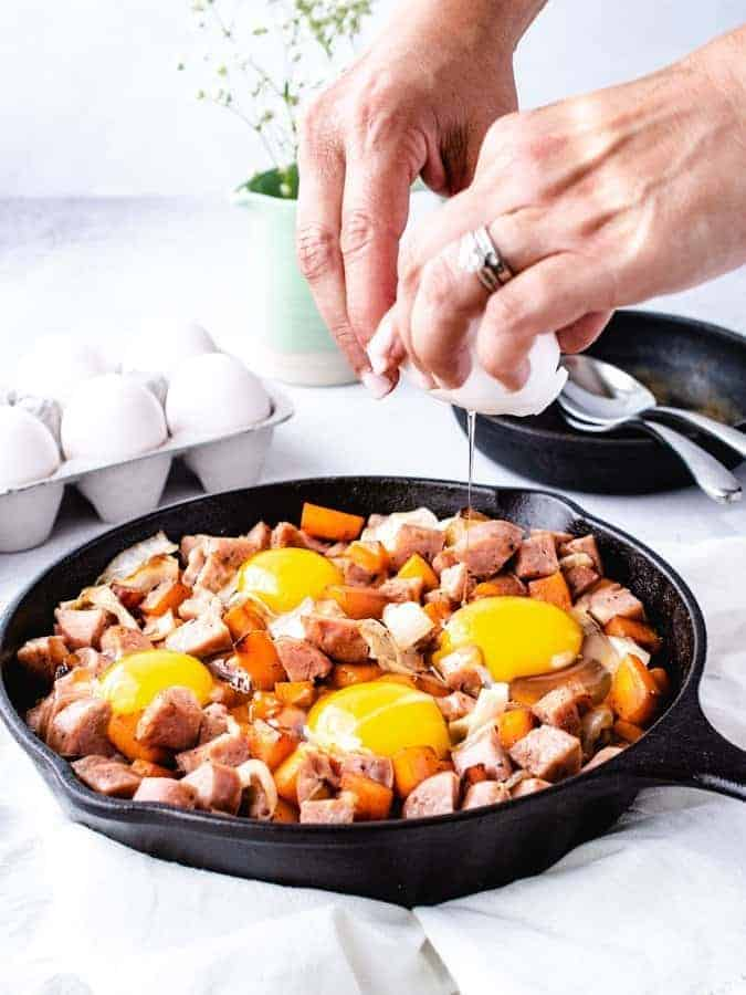 Cracking an egg into paleo breakfast hash