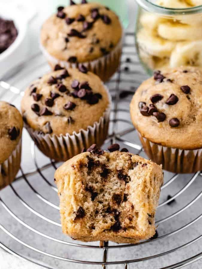 Banana Chocolate Chip Muffins on a wire rack with a bite taken out