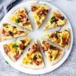 Horizontal image of sliced cauliflower crust breakfast pizza