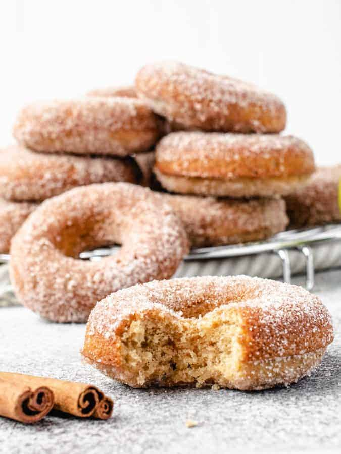 Pile of baked apple cider donuts with one in front with bite taken out