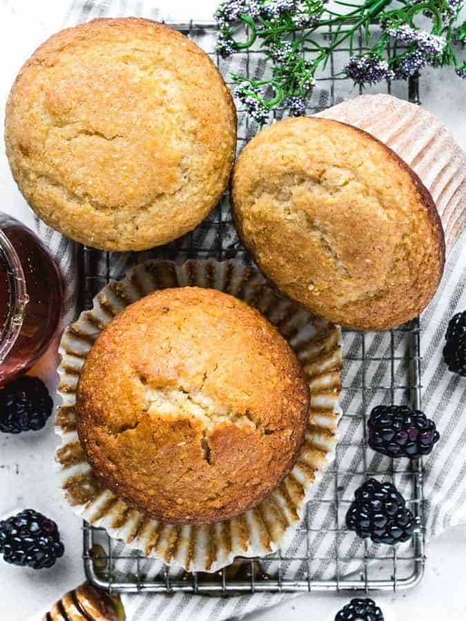 Overhead photo of jumbo corn muffins with honey and blackberries around