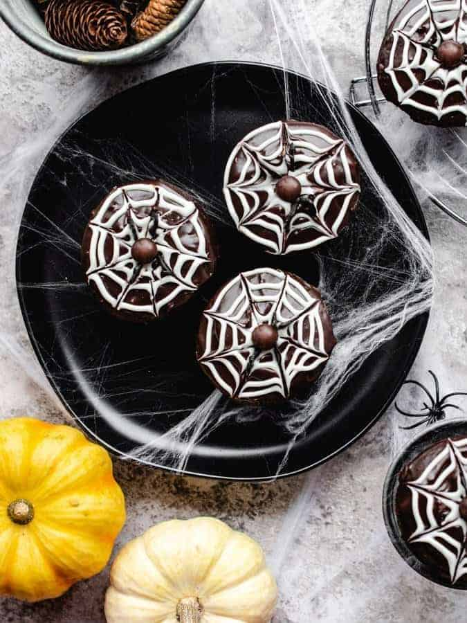 Overhead photo of halloween spider cupcakes on a plate with spiderwebs around
