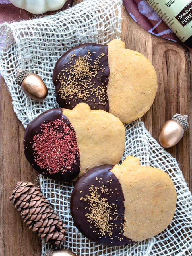 Overhead photo of 3 pumpkin sugar cookies dipped in chocolate with sprinkles