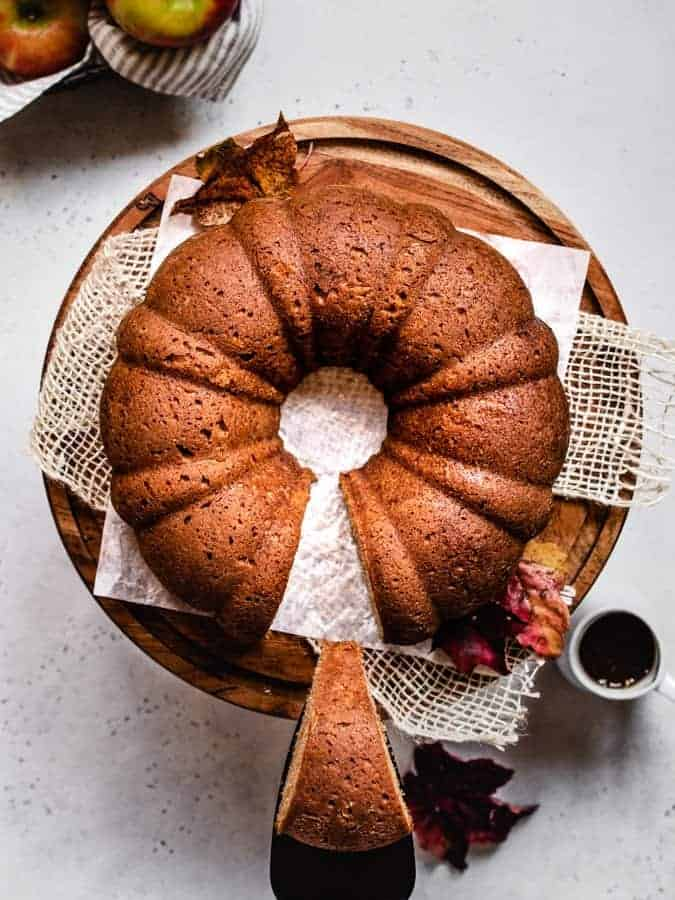 Overhead photo of applesauce cake on a cake stand lifting one slice out of the cake