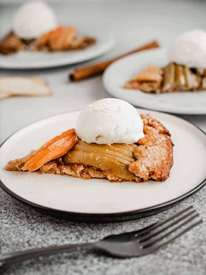 slice of maple apple galette on a plate with scoop of vanilla ice cream on top