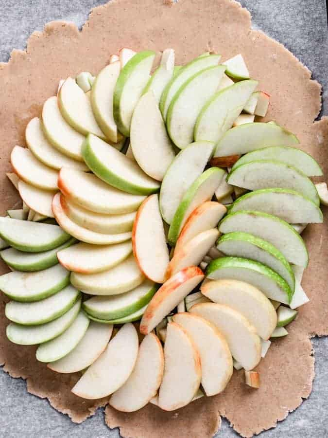 Maple Apple Galette filling with apples arranged in pattern on rolled out dough