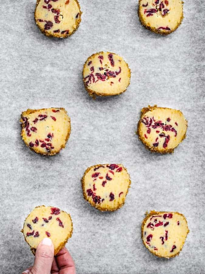 Overhead flatly of orange cranberry shortbread cookies on sheet tray