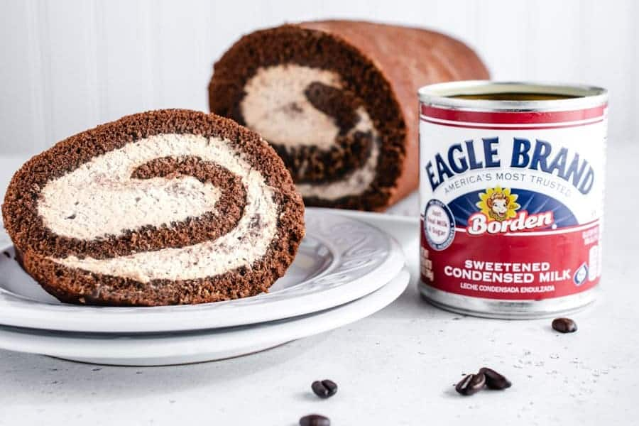 Horizontal image of Vietnamese coffee Swiss roll cake with can of sweetened condensed milk next to it