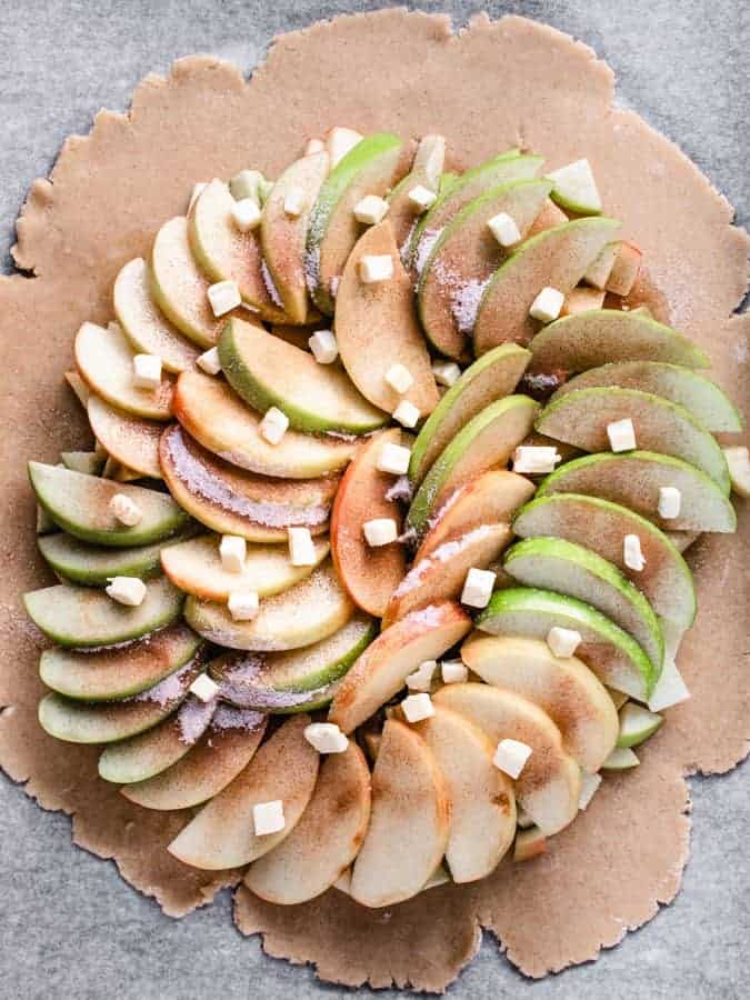 Maple Apple Galette with apples arranged on dough and dotted with butter