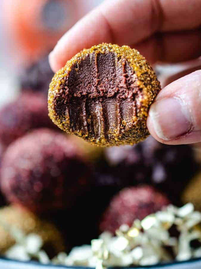 Chocolate Pumpkin Truffles with bite taken out, being held up