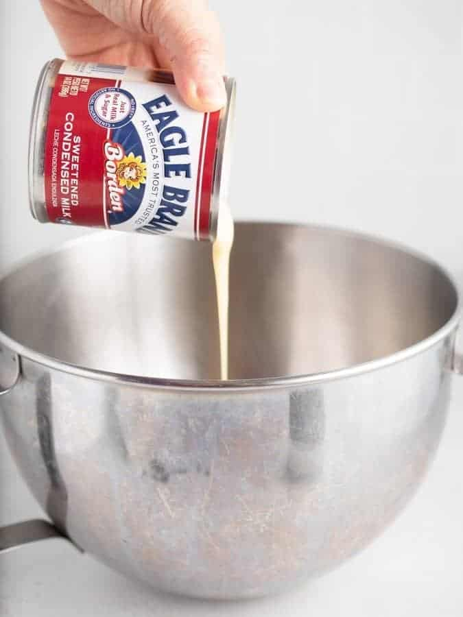 Pouring sweetened condensed milk into mixing bowl