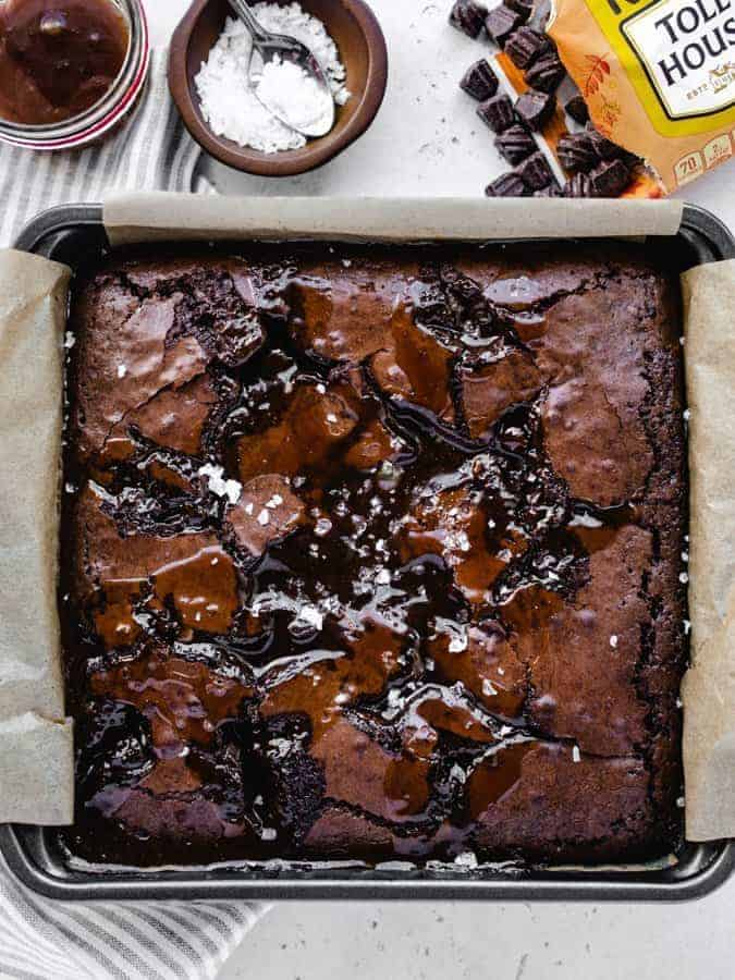 Overhead image of freshly baked salted caramel brownies in a square pan lined with parchment paper