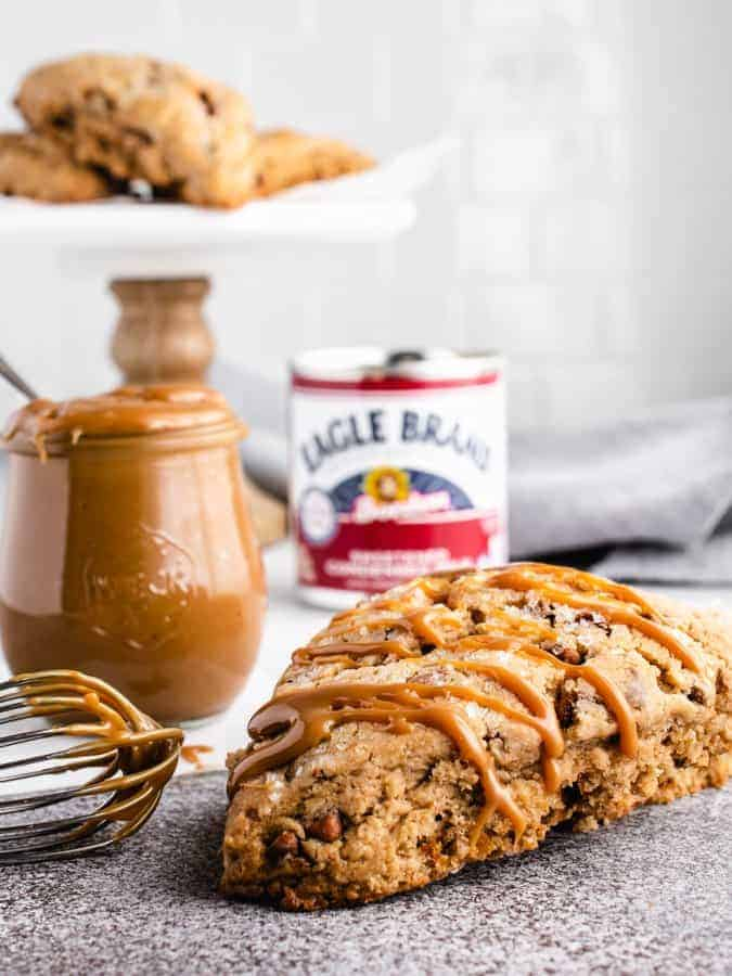 Dulce de leche scone with whisk and jar of dulce de leche next to it
