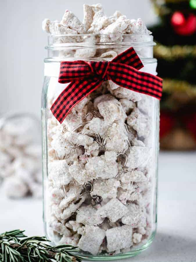 Jar of peppermint puppy chow with christmas ribbon on it