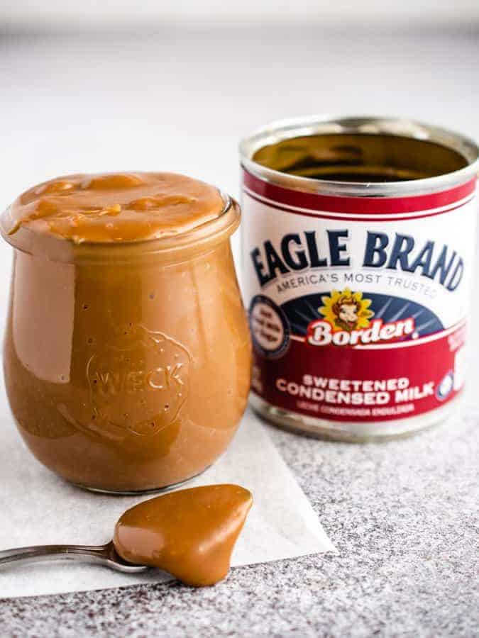 Jar od dulce de leche with spoonful in front and can of sweetened condensed milk next to it