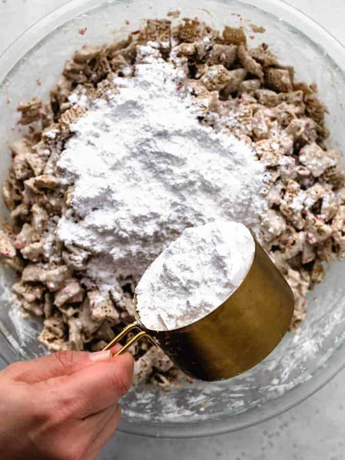 Mixing powdered sugar to make peppermint puppy chow