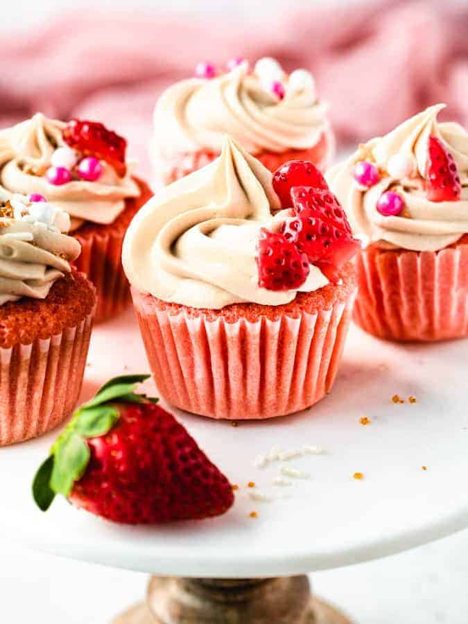 Pink champagne cupcakes on a cake stand with strawberry in front