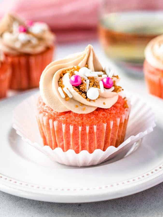 Pink champagne cupcake on a plate with cupcakes around it