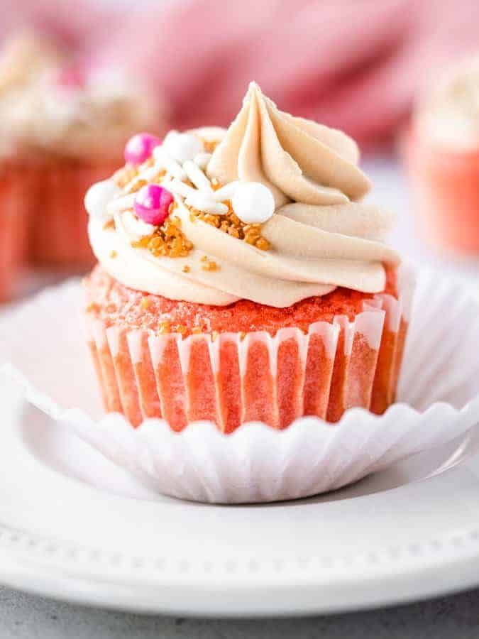 Close up of pink champagne cupcake on a white plate with sprinkles on top