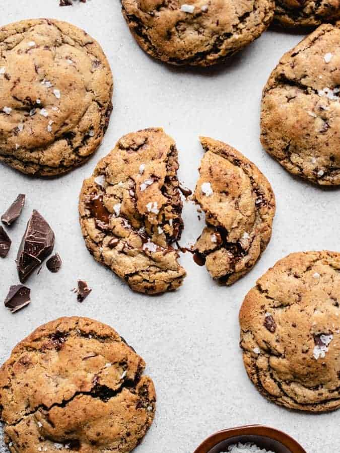 overhead of chocolate chunk cookies, middle cookie split in half with melted chocolate
